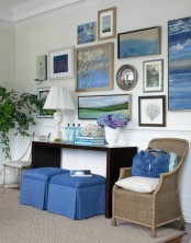 a dark console, a large gallery wall with seascapes, a rattan chair and touches of bright blue