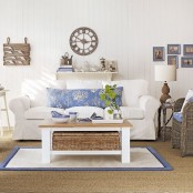 a traditional beach living room with white upholstered and rattan furniture, touches of blue and sea-inspried artworks