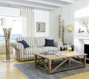 a coastal living room with a view, a striped sofa, a wooden coffee table, strands of seashells and a driftwood lamp
