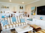 a neutral beachy living room with a striped sofa, a built-in shelving units with items on display and some sea-inspired accessories