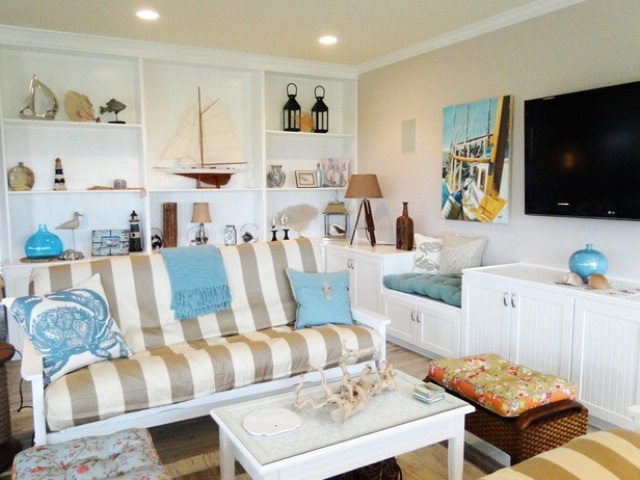 a neutral beachy living room with a striped sofa, a built in shelving units with items on display and some sea inspired accessories