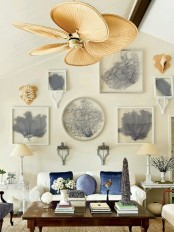 an attic beach living room with a white sofa, blue pillows and a large gallery wall with beautiful art pieces plus a rattan fan