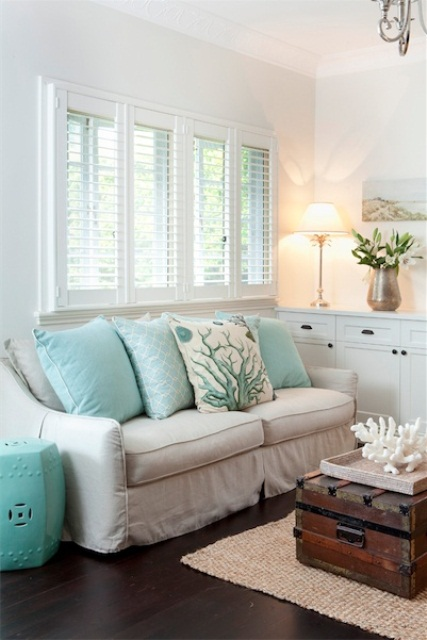 a small white beach living room with touches of turquoise, a stained chest for storage and an artwork