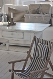 a neutral coastal living room with whitewashed furniture and striped decor for a vintage feel