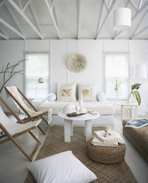 a relaxed white living room with jute ottomans and rugs, folding beach chairs, printed pillows