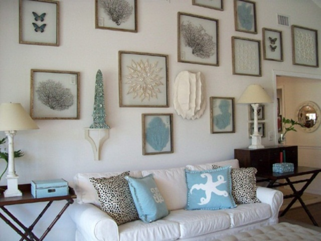 a neutral beachy living room with white furniture and a large gallery wall with sea creatures plus stained tables
