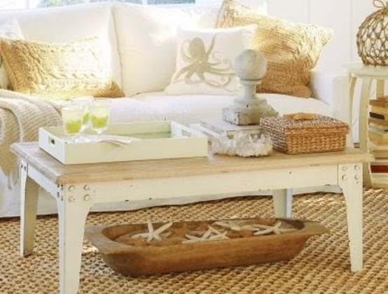 a sunlit beach living room with a wooden coffee table, baskets and a dough bolw plus sea-inspired pillows