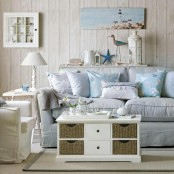 a neutral and powder blue living room with whitewashed wood walls, vintage upholstered furniture and a coffee table with basket drawers
