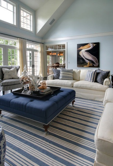 a blue and navy beach living room with stripes, a pelican artwork and much sea-inspired decor on the ottoman