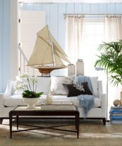 a beachy living room in light blues, with neutral furniture and printed pillows
