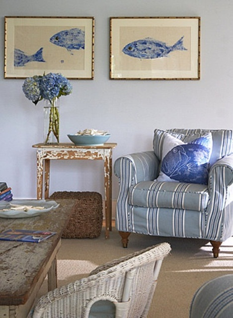 a light blue, grey and tan living room in coastal style with striped and rattan furniture, sea inspired artworks