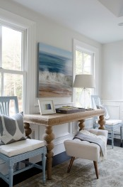 a beachy living room with a gorgeous artwork, light blue chairs, a cork table and a rug