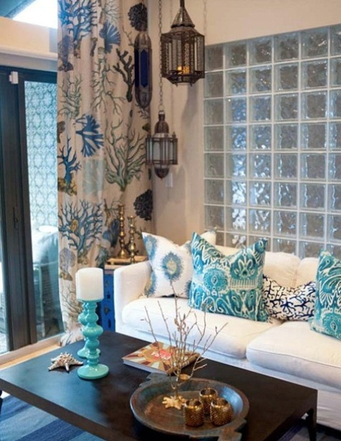 a sea inspired living room with a light blue glass wall, a white sofa with printed pillows, a printed curtain and Moroccan lanterns
