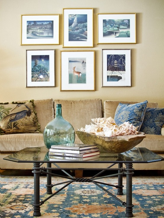 a modern beach living room with sandy walls, a gallery wall with sea-inspired artworks, a glass table and a tan sofa
