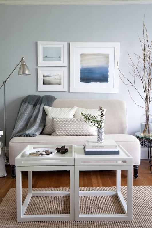 a neutral and light grey beach living room with a small vintage seat, a couple of tables and a sea inspired gallery wall