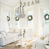 a white coastal living room with white furniture and curtains, a tan rug and a suspended ship
