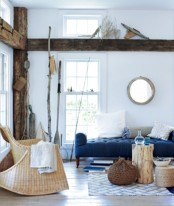a modern coastal living room in navy, white and tan, with much wood, rattan, wicker and some decorative items