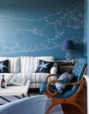 a sea-inspired living room with an accent map blue wall, a matching chair,  a striped sofa and navy lamps