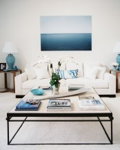 a beahcy living room in cremay and bold blues, a modern coffee table, a large and bold artwork, side tables with blue lamps