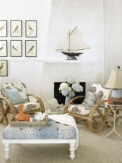 a coastal living room with much tan, creamy, white and blues, boats, rattan chairs and a blue ottoman