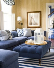 a bold coastal living room with navy upholstered furniture, striped rugs and pillows and corals for decor