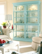 an aqua blue armoire with various corals on display is a cool idea to decorate a sea-inspired living room