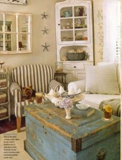 a neutral beachy living room with an aqua blue chest, vintage furniture and a striped chair
