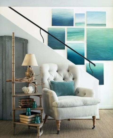 a bold and large sea inspired gallery wall, a white upholstered chair and an etagere with books and aqua accessories