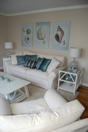 a neutral coastal living room with creamy furniture, a gallery wall of vintage sea posters, white tables
