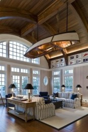 a coastal living room with a boat suspended over the space, striped and navy furniture and vintage lamps