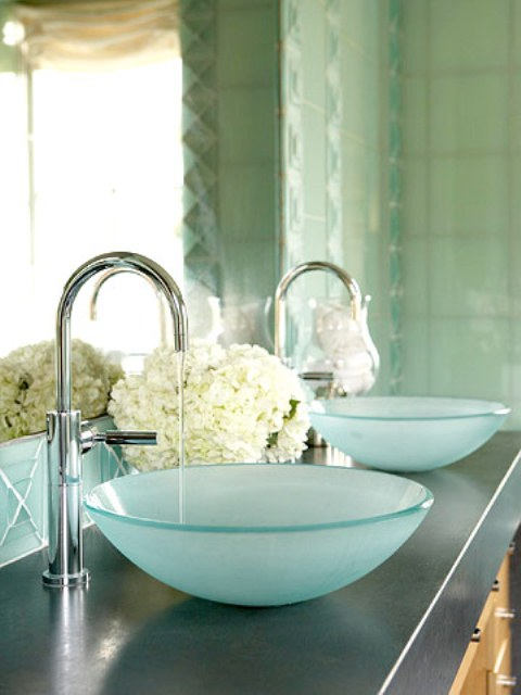 a sink space with two aqua vessel sinks of glass and soem white hydrangeas