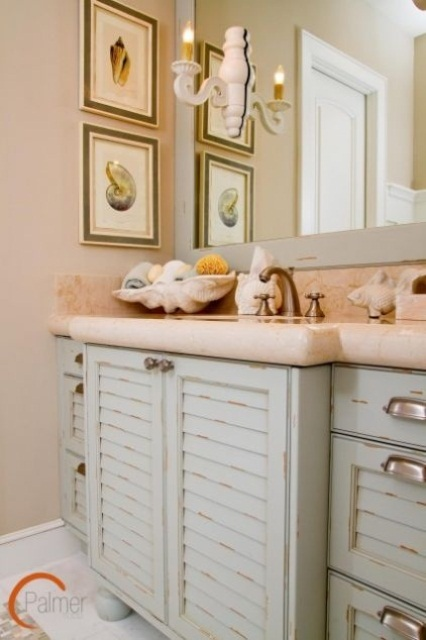 a blush and grey bathroom with a vintage vanity with a pink countertop, sea-inspried artworks and a seashell soap dish