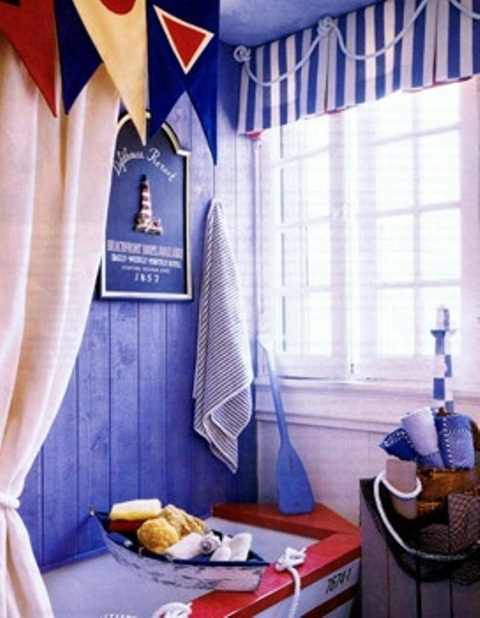 a blue, red and white bathroom with a boat-shaped bathtub, catchy curtains and sponges and towels for a more sea-inspired feel