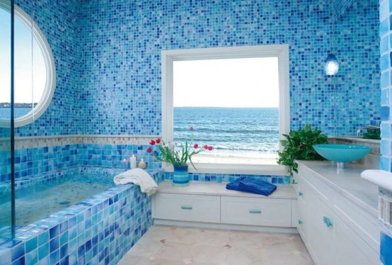 a blue sea-inspired bathroom with mosaic tiles, white furniture and large windows with ocean views