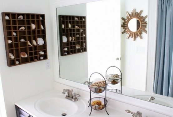 a neutral bathroom with a box shelf with seashells and starfish, a sunburst mirror and a stand with soaps and sponges