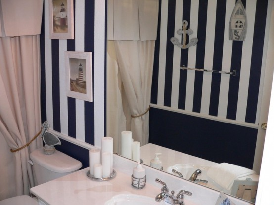 a black and white bathroom with sea-inspired artworks and some appliques on the wall