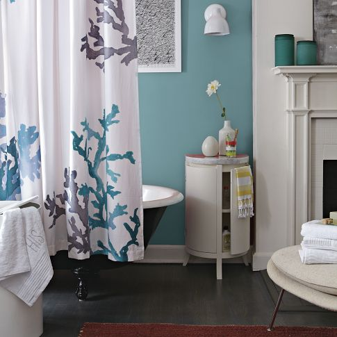 a blue bathroom with a dark floor, a coral print shower curtain, a white table with storage