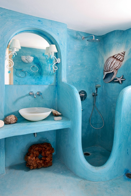 a blue painted plaster bathroom with a carved shower space, lamps, stones, corals and a painted seashell