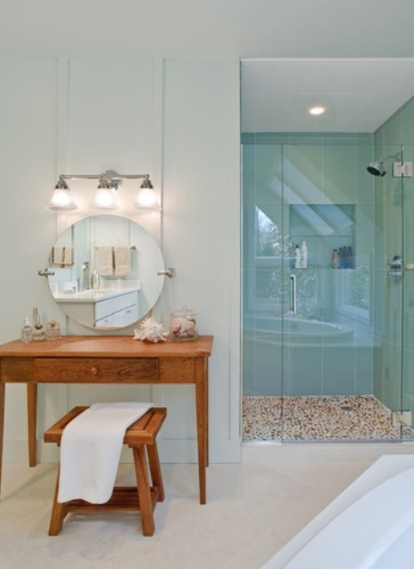 a neutral beachy bathroom with aqua-colored tiles in the shower, a wooden vanity plus a stool and some sea creatures