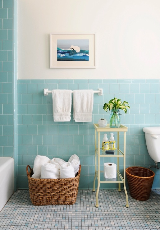 an aqua colored sea bathroom with a mosaic floor, some baskets for storage and a pastel etagere