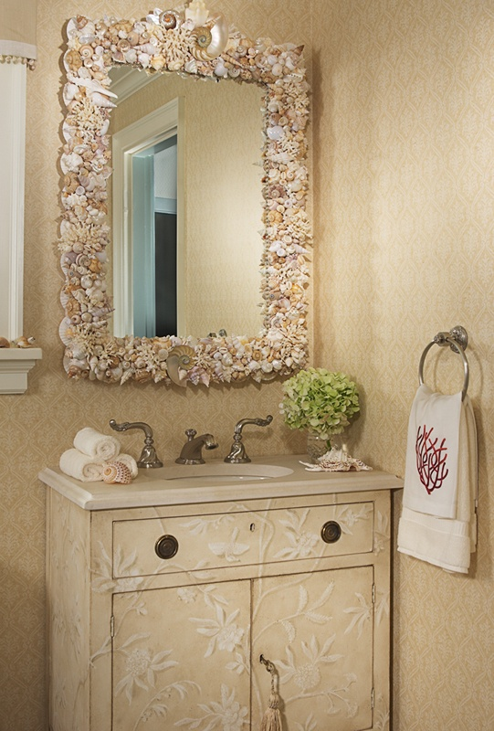a neutral sink space with a textural vanity, a seashell and starfish clad mirror, coral printed towels