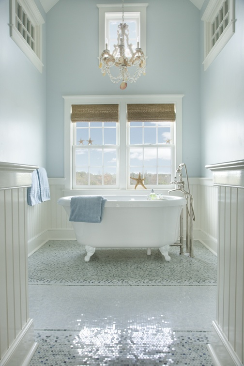 a light blue and creamy bathroom with a mosaic floor, woven Roman shades, a clawfoot bathtub and a chandelier