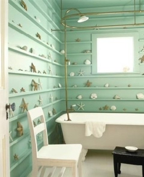 an aqua colored bathroom with lots of ledges along the walls and starfish and seashells plus gold touches
