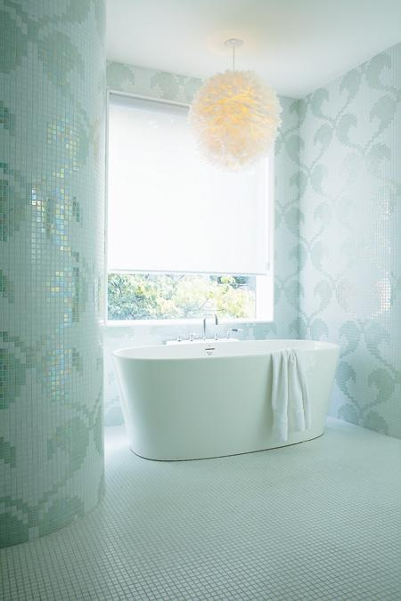 an ocean-inspired bathroom fully clad with aqua-colored mosaic tiles showing off patterns plus a fluffy pendant lamp