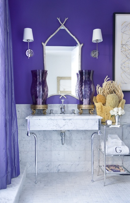 a purple and marble tile bathroom with sponges and corals, with a catchy mirror and large purple lanterns