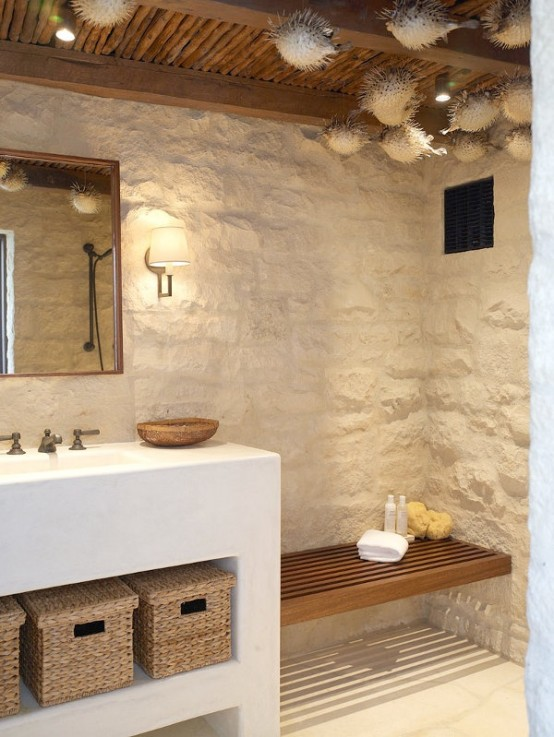 a beach bathroom with stone clad, a white vanity with baskets for storage and faux fish suspended to the ceiling