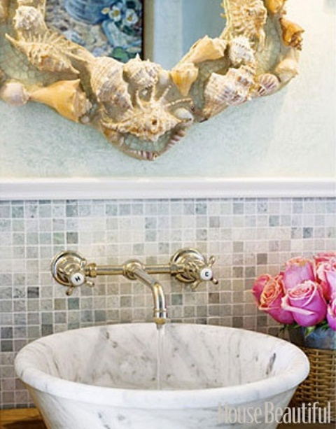 a marble sink and a mirror clad with seashells and starfish for a sea inspired bathroom