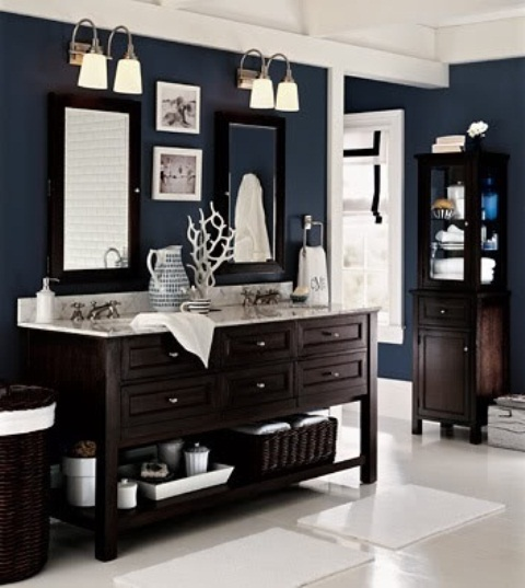 a navy sea bathroom with dark-stained furniture, dark baskets and some white surfaces to create a contrast