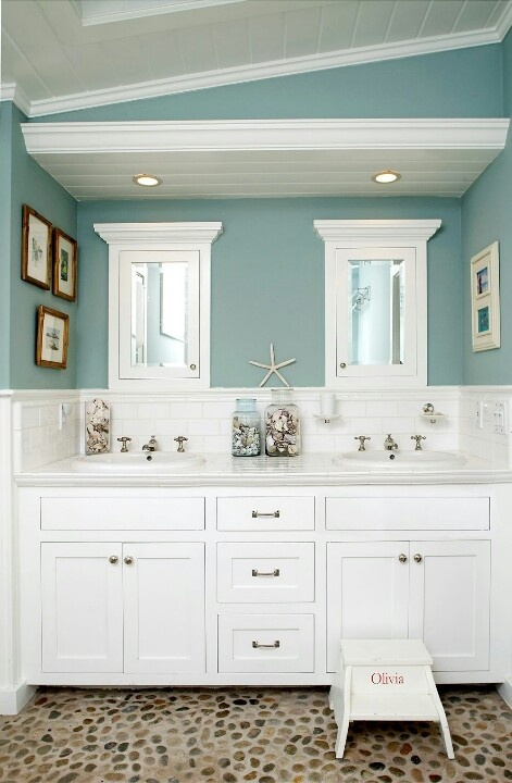 slate blue and white bathroom with a large white vanity, artworks and starfish and seashells