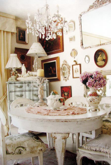 a beautiful shabby chic dining room with gorgeous vintage furniture, a gallery wall with artworks and mirrors, vintage lamps and a crystal chandelier